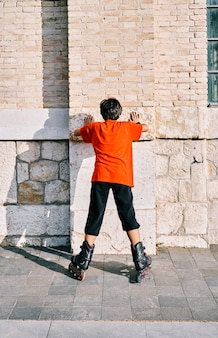 Kaukasischer junge von hinten, der mit rollschuhen spielt und im park an die wand geklebt ist.