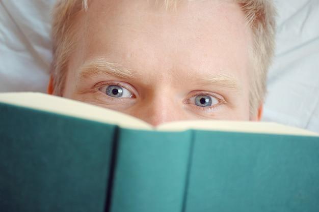 Kaukasischer junger emotionaler fröhlicher mann, der ein buch liest, während er sich hinlegt.
