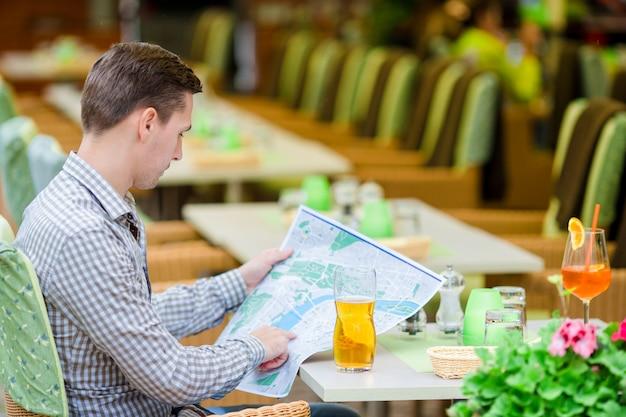 Kaukasischer junger europäischer mann mit stadtplan im freienkaffee. porträt des attraktiven jungen touristen auf mittagspause