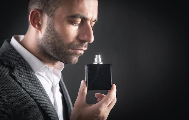 Kaukasischer junger geschäftsmann, der parfüm riecht.