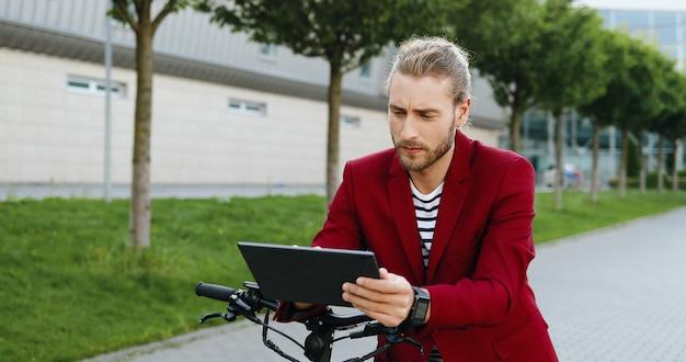 Kaukasischer junger hübscher mann in der roten jacke, die auf straße am elektroroller steht und video auf tablet-gerät sieht. stilvoller typ, der auf gadget-computer tippt und scrollt. sms in sozialen medien.