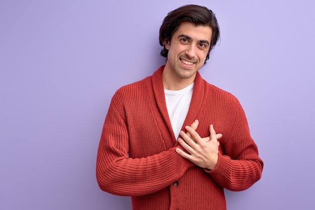 Kaukasischer junger mann, der dankbarkeit mit händen auf brust ausdrückt