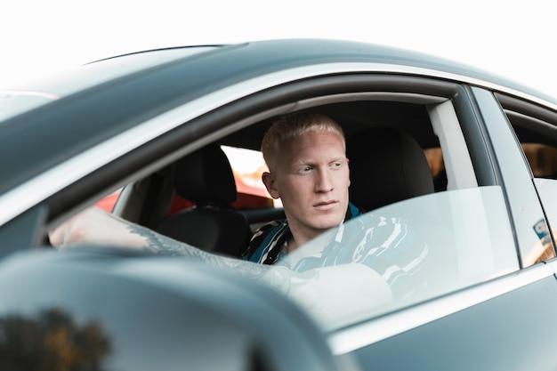 Kaukasischer junger mann, der ein auto fährt