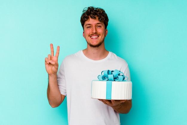 Kaukasischer junger mann, der einen kuchen auf blauem hintergrund isoliert hält und nummer zwei mit den fingern zeigt.