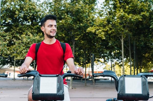 Kaukasischer junger mann, der lächelt, während er auf einem gemieteten fahrrad sitzt