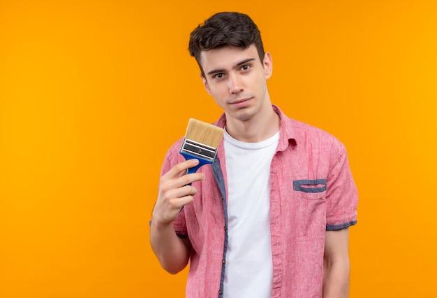 Kaukasischer junger mann, der rosa hemd hält, das pinsel auf isolierter orange wand hält
