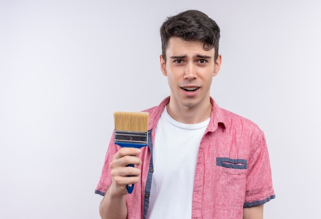 Kaukasischer junger mann, der rosa hemd hält, das pinsel auf isolierter weißer wand hält