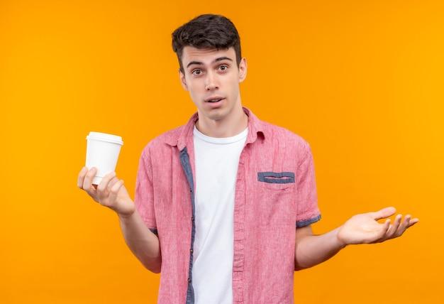 Kaukasischer junger mann, der rosa hemd hält tasse kaffee zeigt, welche geste auf isolierter orange wand