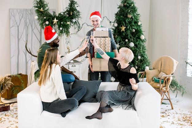 Kaukasischer junger mann, der weihnachtsgeschenke freunden auf dem sofa bei neujahrsparty präsentiert