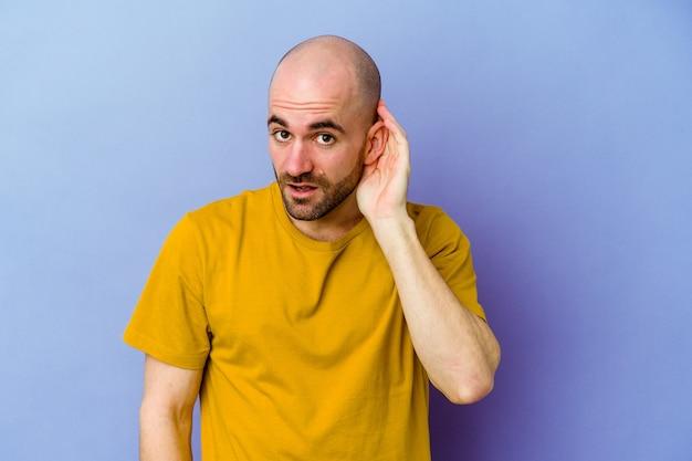 Kaukasischer junger mann mit glatze isoliert auf lila hintergrund, der versucht, einen klatsch zu hören.