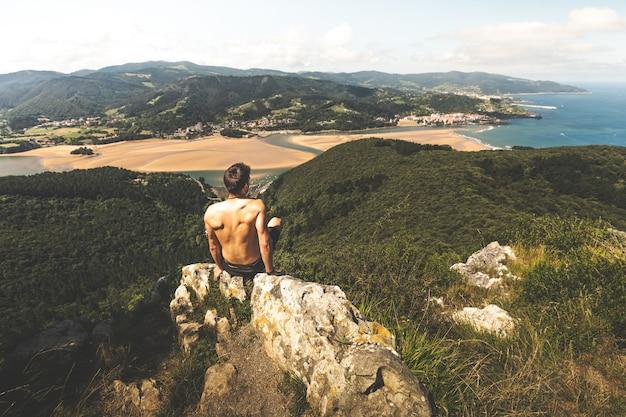 Kaukasischer junger mann mit nacktem oberkörper auf einem berg mit blick auf die mündung des flusses urdaibai neben dem kantabrischen meer in bizkaia; baskenland.
