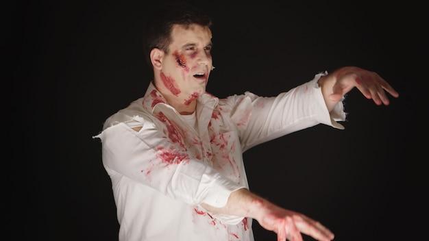 Kaukasischer junger mann verkleidet wie ein zombie aus horrorfilm für halloween.