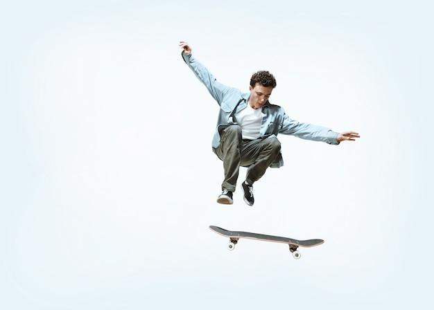 Kaukasischer junger skateboardfahrer reitet isoliert auf weiß