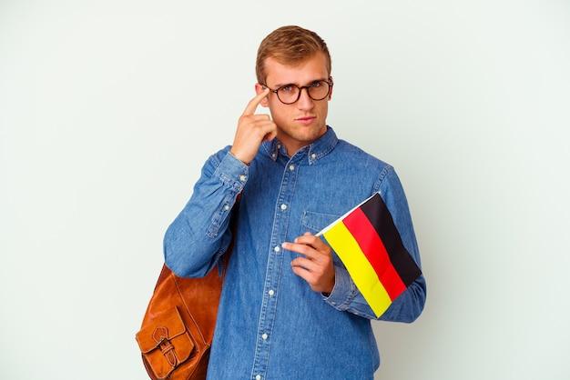 Kaukasischer junger student, der deutsch studiert, lokalisiert auf weißer wand, die tempel mit finger zeigt, denkend, fokussiert auf eine aufgabe.