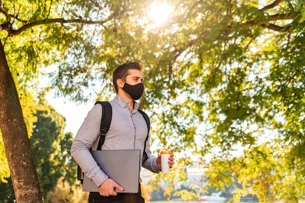 Kaukasischer junger student und arbeiter mann, der eine gesichtsmaske trägt, kaffee zum mitnehmen trinkt und seinen laptop in einem schönen park an einem sonnigen tag trägt. speicherplatz kopieren.