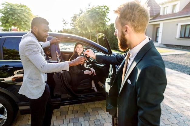 Kaukasischer junger verkäufer, der schlüssel zum jungen afrikanischen geschäftsmann nach dem kauf eines autos behandelt. junge kaukasische geschäftsdame sitzt im auto