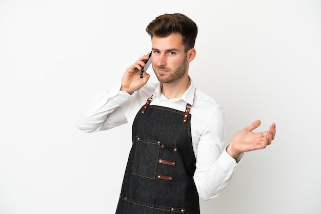 Kaukasischer kellner im restaurant isoliert auf weißem hintergrund, der ein gespräch mit dem mobiltelefon mit jemandem führt