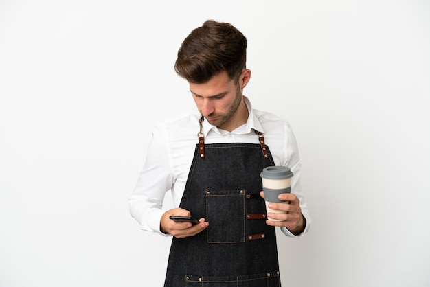 Kaukasischer kellner im restaurant isoliert auf weißem hintergrund mit kaffee zum mitnehmen und einem handy