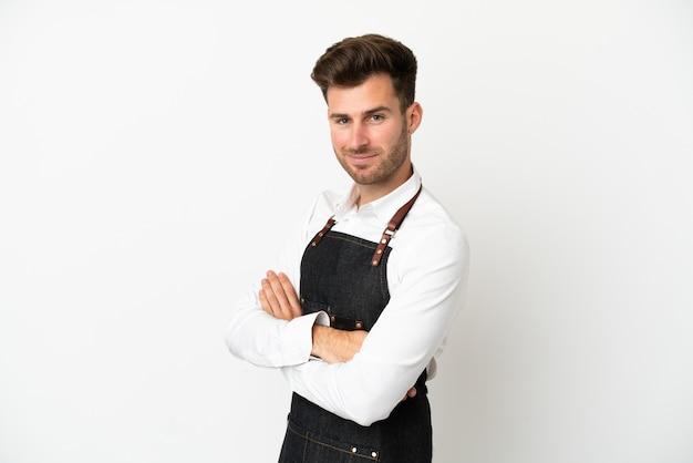 Kaukasischer kellner im restaurant isoliert auf weißem hintergrund mit verschränkten armen und freut sich
