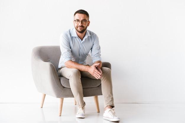 Kaukasischer kerl, der stilvolle formelle kleidung trägt, die im sessel sitzt und kamera betrachtet, lokalisiert auf weiß