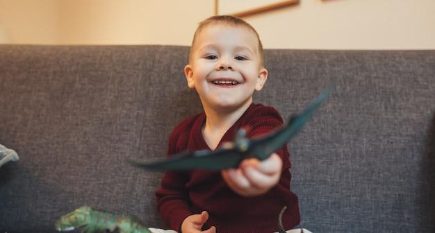 Kaukasischer kleiner junge, der auf dem sofa sitzt und mit dinosaurierspielzeugen spielt