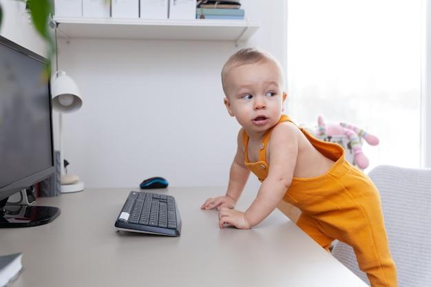 Kaukasischer kleiner junge mit lustigem gesichtsausdruck versuchen, computer, monitor und tastatur zu erforschen,