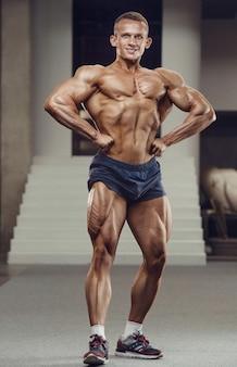 Kaukasischer kraftsportler, der beinquadrizepsmuskeln aufpumpt. starker bodybuilder mit sixpack, perfekter bauchmuskulatur, trizeps, brust, schultern im fitnessstudio. fitness- und bodybuilding-konzept