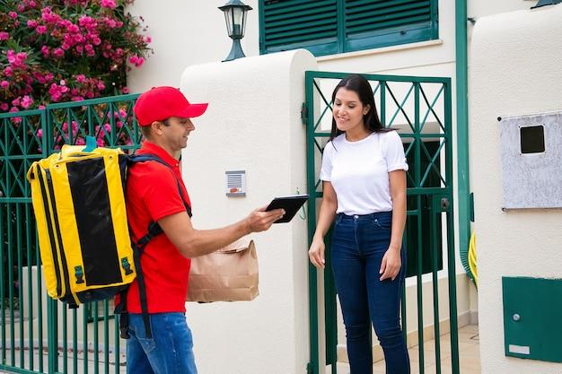 Kaukasischer kurier, der bestellung zum kunden liefert und daten in der zwischenablage anzeigt. professioneller lieferbote, der gelben rucksack und paket trägt. frau beobachtet auf papier. lieferservice und postkonzept