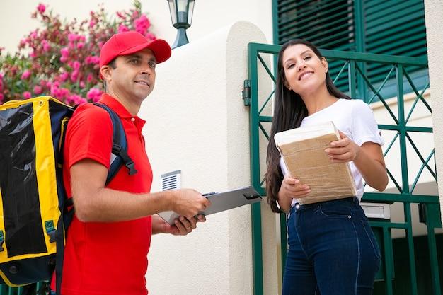Kaukasischer lieferbote, der rote uniform hält, die klemmbrett vor haus hält. schöne brünette frau, die paket oder schachtel vom postboten annimmt und lächelt. hauslieferdienst und postkonzept