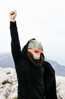Kaukasischer männlicher aktivist, der eine dinosauriermaske und einen umhang trägt, der seine faust in der sierra de tramuntana-bergkette, palma de mallorca, spanien hebt.