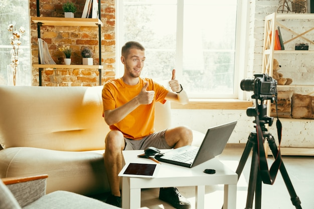 Kaukasischer männlicher blogger mit kameraaufzeichnung videoüberprüfung von gadgets zu hause