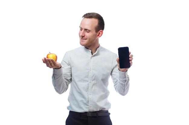 Kaukasischer männlicher geschäftsmann, der ein handy im schwarzen hält und einen rot-gelben apfel hält. er trägt ein hemd. emotionales porträt. isoliert auf weißem hintergrund