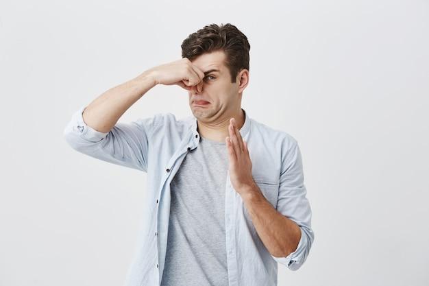 Kaukasischer männlicher hipster mit dunklem haar gekleidet in hellblauem hemd über grauem t-shirt, das nase wegen des schlechten geruchs von etwas schmutzigem und stinkendem klemmt, mit angewidertem ausdruck schauend.