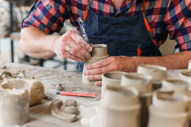 Kaukasischer männlicher töpfer, der keramikkappe in der keramik macht.
