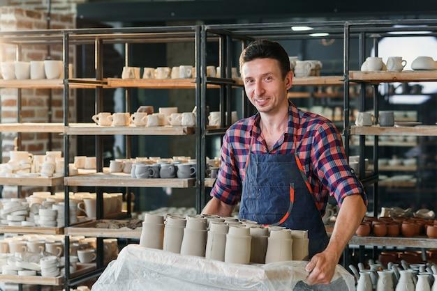 Kaukasischer männlicher töpfer, der tablett mit keramiktöpfen in der keramik hält.