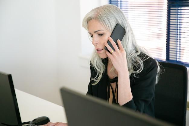 Kaukasischer manager, der am tisch sitzt und über smartphone spricht. schöne nachdenkliche geschäftsfrauen mittleren alters, die im büro arbeiten und auf monitor schauen. geschäfts-, ausdrucks- und berufskonzept