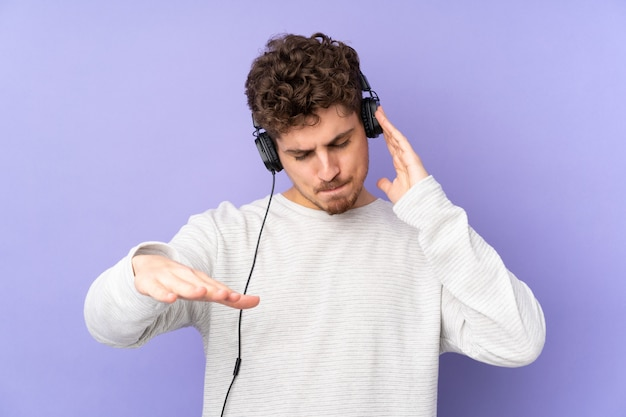 Kaukasischer mann auf lila wand, die musik hört und tanzt