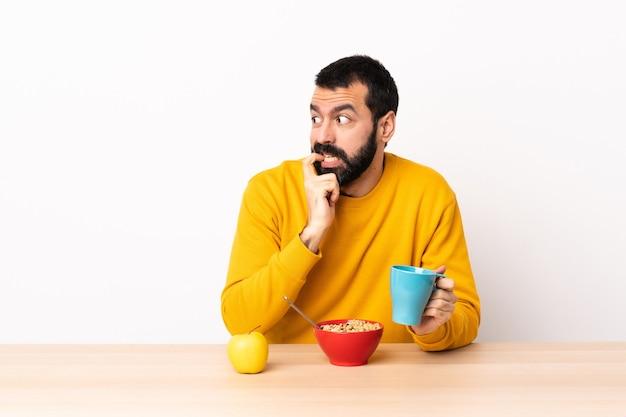 Kaukasischer mann beim frühstück in einem tisch nervös und verängstigt.