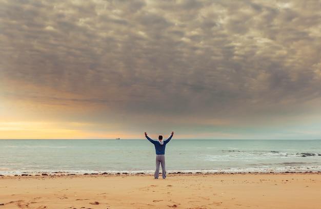 Kaukasischer mann, der am ozeanwasser auf strand bei sonnenuntergang und angehobener hand steht