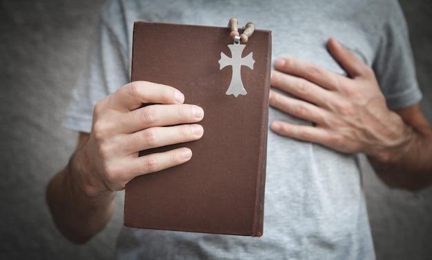 Kaukasischer mann, der bibel und christliches kreuz hält.