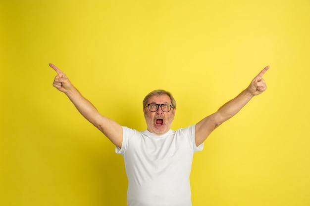Kaukasischer mann, der den sieg feiert, isoliert auf gelb