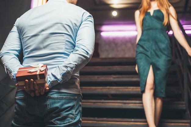 Kaukasischer mann, der ein geschenk für seine frau am valentinstag versteckt, ein hemd tragend und das ingwermädchen aufblickend