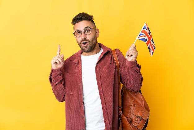 Kaukasischer mann, der eine auf gelb isolierte flagge des vereinigten königreichs hält, die beabsichtigt, die lösung zu realisieren, während er einen finger anhebt