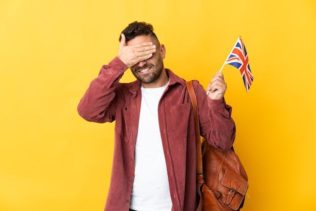 Kaukasischer mann, der eine britische flagge lokalisiert auf gelbem hintergrund hält, der augen durch hände bedeckt. ich will nichts sehen