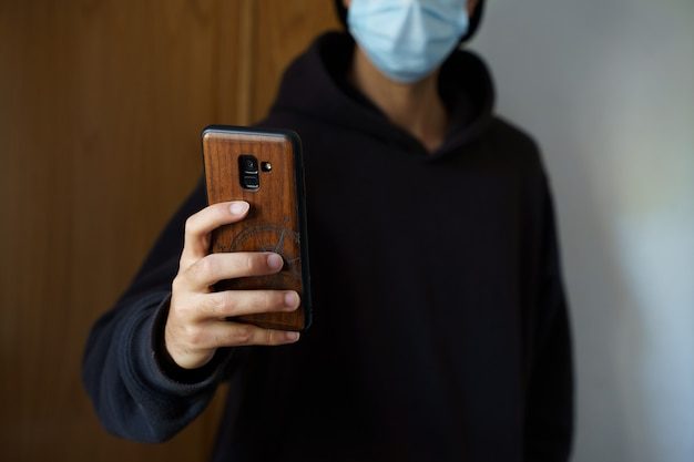 Kaukasischer mann, der eine chirurgische maske trägt und mit seinem smartphone ein selfie macht. palma de mallorca, spanien