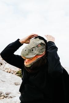 Kaukasischer mann, der eine dinosauriermaske und einen umhang trägt, überrascht und hält seine hände an den kopf in der sierra de tramuntana, palma de mallorca, spanien