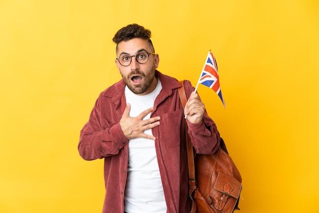 Kaukasischer mann, der eine flagge des vereinigten königreichs isoliert auf gelb hält, überrascht und schockiert, während er nach rechts schaut