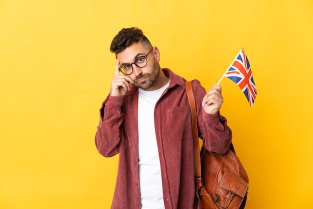 Kaukasischer mann, der eine flagge des vereinigten königreichs lokalisiert auf gelber wand hält, die eine idee denkt