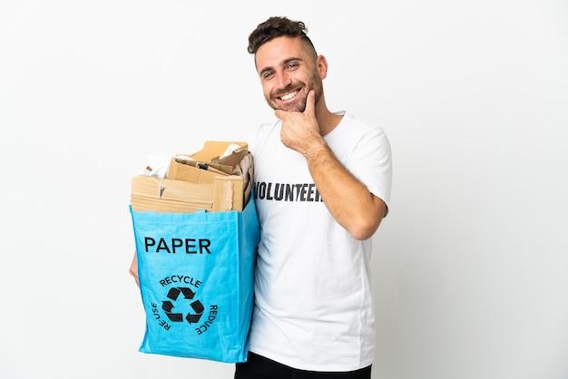 Kaukasischer mann, der eine recycling-tasche voll papier hält, um lokalisiert auf weißem hintergrund glücklich und lächelnd zu recyceln