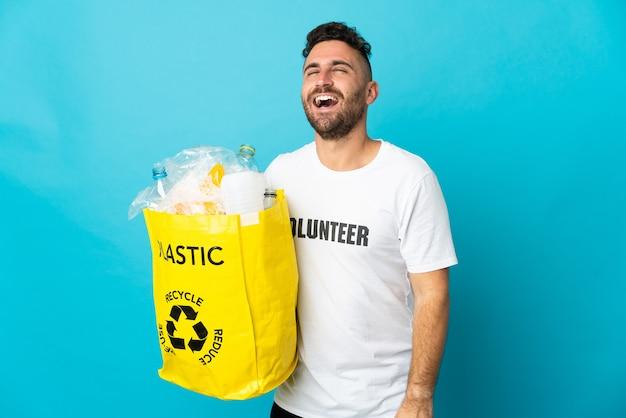 Kaukasischer mann, der eine tasche voller plastikflaschen hält, um lokalisiert auf blauem hintergrund lachend zu recyceln